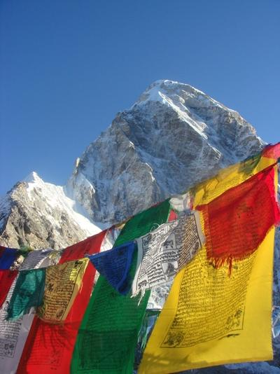 A beautiful view of prayer flags at snow from the bottom of the Himalayas by a volunteer in Nepal