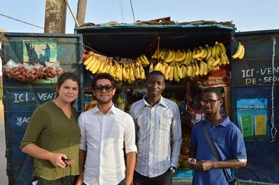 Volunteers with a Senegalese man who runs a business funded by the Microfinance Project.