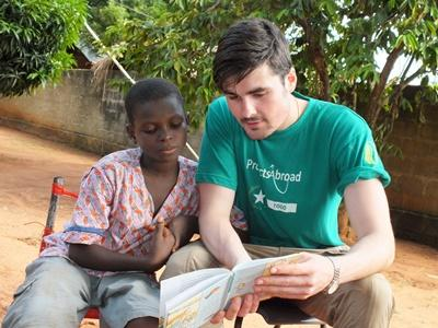 A Projects Abroad volunteer reads aloud to a child at a Care Project in Togo, Africa.