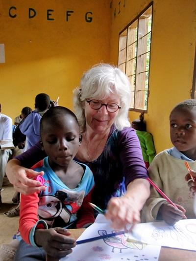 A volunteer helping a child complete their activities on a Care project in Tanzania