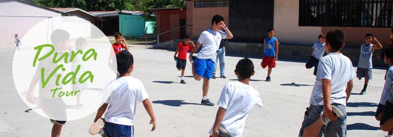 Projects Abroad volunteer coach teaching a stretch to children at a sports project in Heredia, Costa Rica