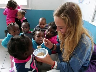 Female volunteer feeds child in South Africa