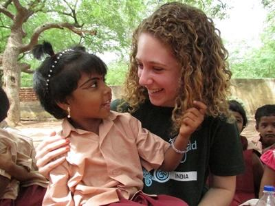 Volunteer and young child sharing a laugh outside a project placement in India