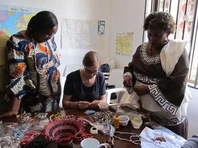 Women and volunteer weave baskets on the Microfinance project in Ghana, West Africa