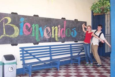 Interns on a project in Costa Rica, Central America pose in front of a welcome sign