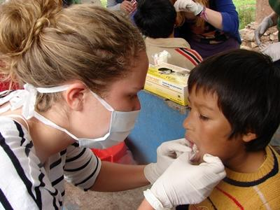 A Projects Abroad Dentistry volunteer helps a Peruvian child