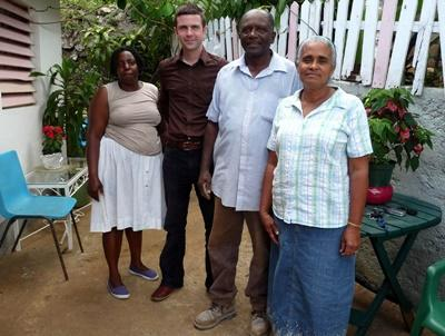 Host family and volunteer outside host home in Jamaica