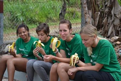 A group of volunteers relax and eat fresh fruit at their placement in Jamaica