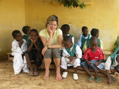 Volunteer sitting on a bench with a group of children in Senegal