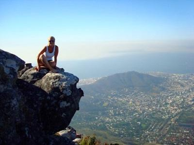 Volunteer sitting on top of Lions Head Mountain while traveling in South Africa
