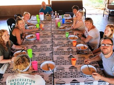 A group of Projects Abroad Conservation volunteers have a meal at their accommodation at Wild at Tuli in Botswana