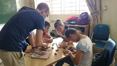 Projects Abroad Care volunteer helps children with an activity at his placement in Vietnam, Southeast Asia.