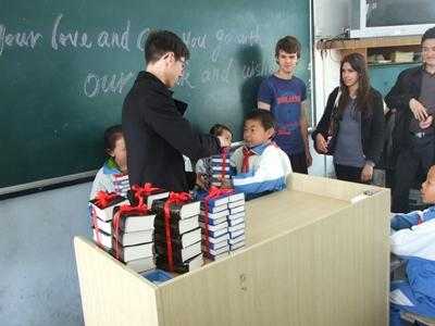Teaching volunteer giving students books in a classroom in Asia