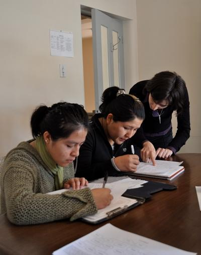 Volunteers assists students with the classwork on a Teaching project in Latin America