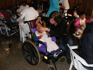 Volunteer assists child in a wheelchair at a hospital placement on the Care project in South America