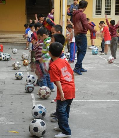 Children practicing soccer with their volunteer sports coach at a school in South East Asia