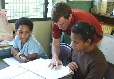 Volunteer on the Teaching project in the South Pacific assisting students with their math classwork