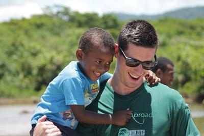 Volunteer holding a young boy at a care center on the Care project in the South Pacific