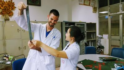 A medical student examines x-rays with a doctor in Vietnam during his internship abroad