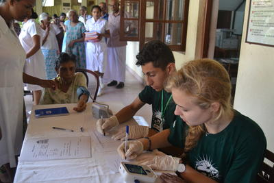 Two gap year students record patient information during a medical outreach in Sri Lanka