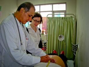Volunteer working with local staff to perform a check up for women on the midwifery project