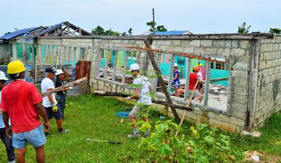 Internation Volunteers come together to rebuild structures on a Disaster Relief program in the Philippines