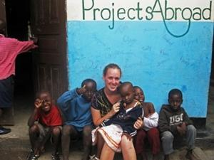 A group of local school children pose with a Care volunteer on a project in Tanzania