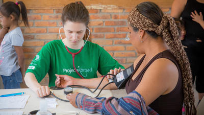 A college student measures blood pressure during a short-term volunteer abroad trip to Mexico