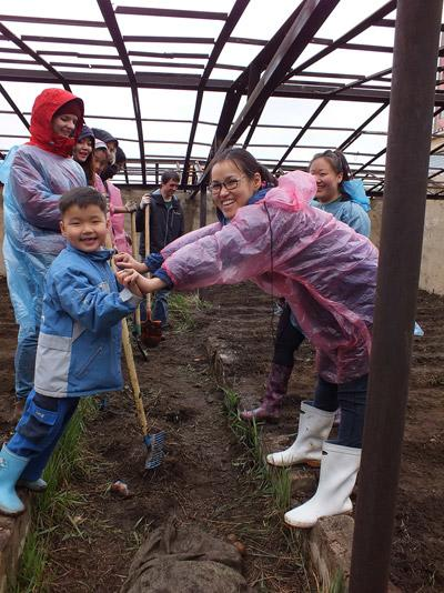 Short Term Volunteers playing with local children on a Farming Project Abroad