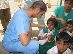 Last Minute Medicine volunteer playing with children outside of the Medicine project placement