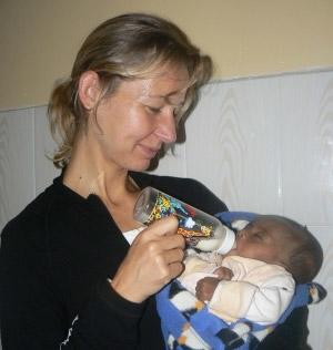Older volunteer feeding a bottle to a child on a project in Ethiopia with Projects Abroad