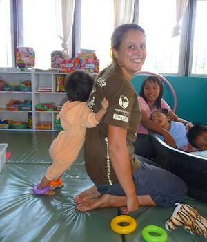Young child hugs Physical Therapy volunteer in a clinic in Thailand