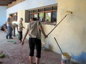 Volunteers painting a school building on a service trip abroad