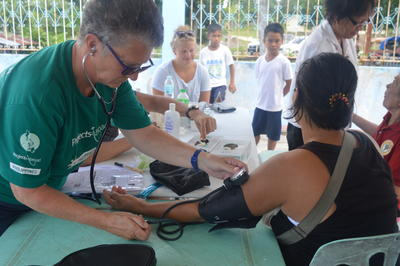 A senior woman works at a medical outreach in the Philippines on her volunteer vacation