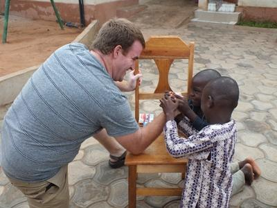 Volunteer overseas arm wrestling with children on a Care project