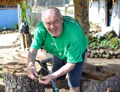 A senior volunteer abroad plants seedlings at a Nutrition Project in Fiji