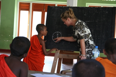 Female volunteer teaching young monks about reading time in a school in Sri Lanka