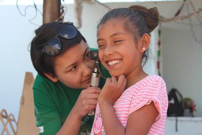 A child in Mexico has her ears checked by a college student volunteering on a medical program.