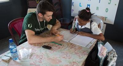 A child gets help with reading from a college student participating in a volunteer program in Belize.