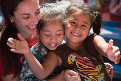 Two Costa Rican girls enjoy the company of a volunteer on her mission trip