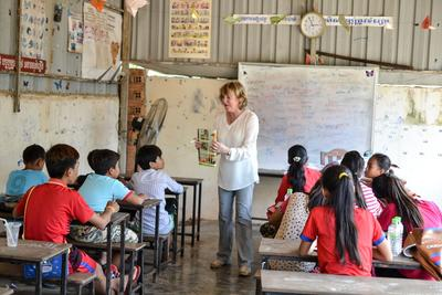 A group of school children listen to an older adult teach on her international volunteering opportunity in Cambodia.
