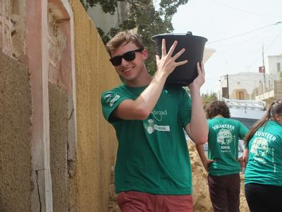A volunteer carries sand on his building international volunteer opportunity based in Senegal.