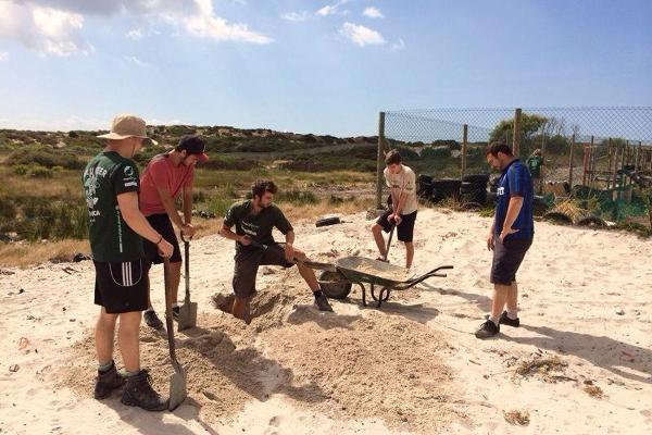 A group of Projects Abroad volunteers dig sand for building a new community center in Cape Town, South Africa.