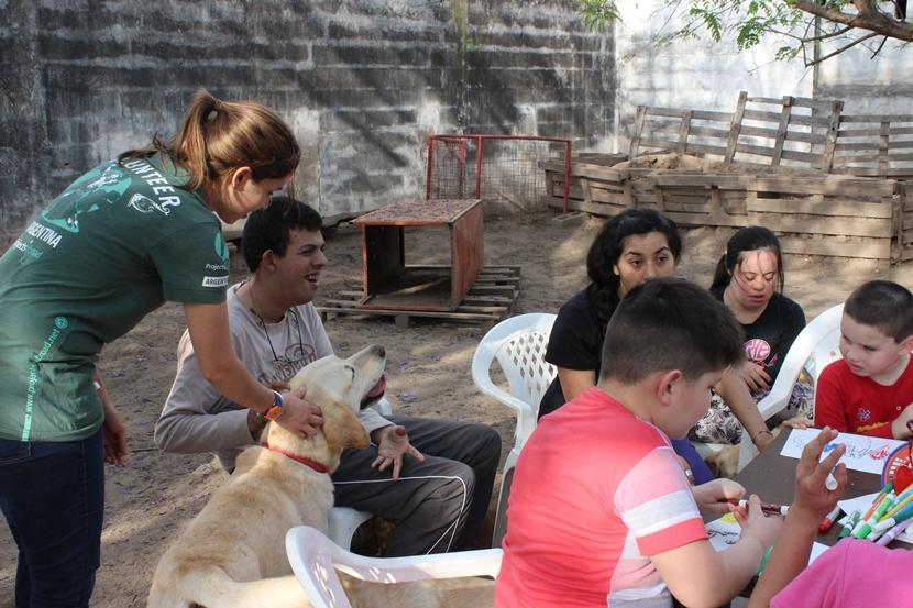 A Projects Abroad volunteer helps a disabled young man interact with a trained therapy dog in Argentina.