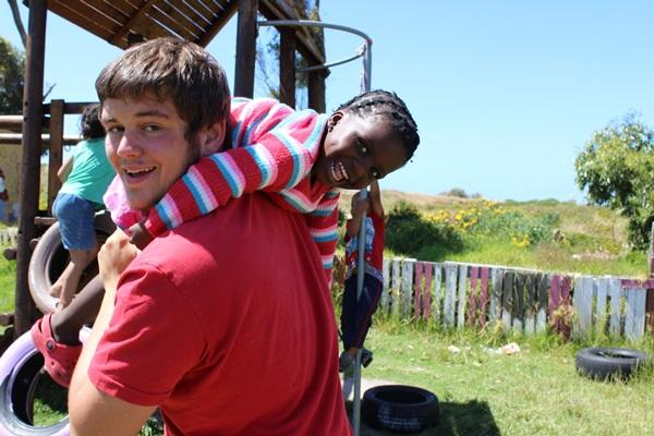 Male volunteer with a child in South Africa.