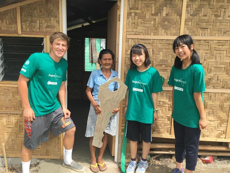 Projects Abroad building volunteers present the key to a newly built house to a Typhoon Haiyan survivor
