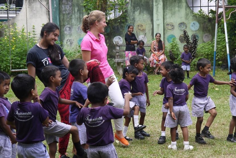 Projects Abroad volunteers play a game outdoors with children at a care center in Sri Lanka.
