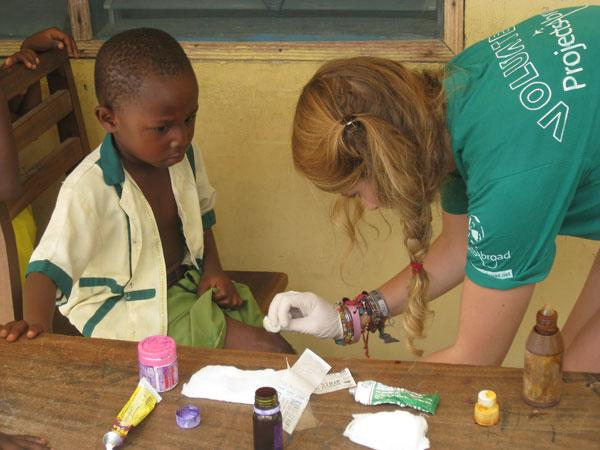 Volunteer working with a child in a community medical outreach