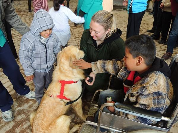 Bolivian children pet a therapy dog under the supervision of a Canine Therapy volunteer