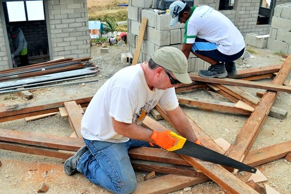 A Disaster Relief volunteer helps build a house for a family displaced by Typhoon Haiyan in the Philippines.